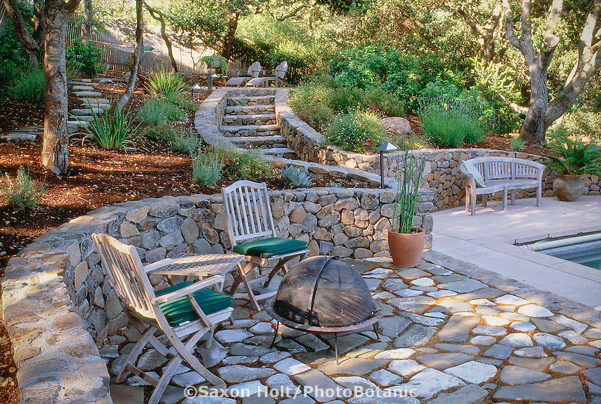Portable fire pit and chairs on stone patio, retaining rock wall and stone steps under oak trees, backyard Californai garden design by Nancy Driscoll