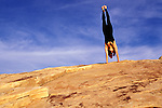woman doing handstand on large rock against blue sky