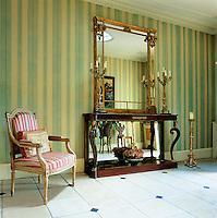 A vestibule is painted in Regency eau-de-nil stripes by Michael Daly. The Regency gilt-framed mirror and table were found in Dublin.