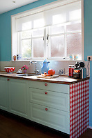 The kitchen units have been painted a pale mint green and coordinated with red and white polka dot handles and a gingham end panel