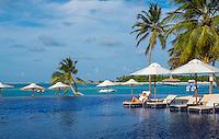 Maldives, Rangali Island. Conrad Hilton Resort. Woman relaxing at the pool near the beach (MR)