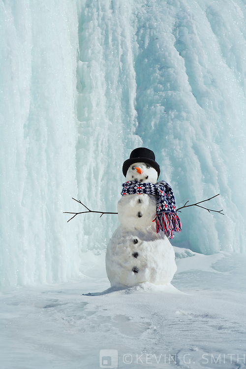 Snowman in front of frozen waterfall, black top hat, blue scarf, sunshine,  Parks Highway, Alaska, USA