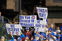 Chicago Cubs fans hold up signs in the seventh inning during Game 5 of the Major League Baseball World Series against the Cleveland Indians on October 30, 2016 at Wrigley Field in Chicago, Illinois.  (Mike Janes/Four Seam Images)
