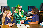 Woman teacher dressed as a leprechaun for St. Patrick's Day gives sticker to.happy black girl in uniform at school with white blonde girl watching.