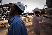 Li Qi (right), a motion engineer, speaks on the phone while operating a crane at the plant site and directing nearby Indian workers at the construction site of the Adani Power plant of 4620 MW capacity in Mundra port industrial city of Gujarat, India. Indian power companies have handed out dozens of major contracts to Chinese firms since 2008. Adani Power Ltd have built elaborate Chinatowns to accommodate Chinese workers, complete with Chinese chefs, ping pong tables and Chinese television. Chinese companies now supply equipment for about 25% of the 80,000 megawatts in new capacity.