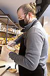 WOLCOTT CT. - 13 January 2020-011321SV04-Luigi Barolli prepares a bagel and cream cheese while working at Wolcott Bagels in Wolcott Wednesday. The new business sells bagels made in Waterbury by Ami's Crispy Bagels.<br /> Steven Valenti Republican-American