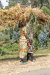 Woman Transporting Grasses On Head Walking With Young Boy