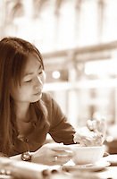 June 16 , 2002, Montreal, Quebec, Canada<br /> <br /> A Japanese tourist enjoy the French culture of Montreal<br /> by eating  a chololate croissant and caffe latte (coffee with milk) in a Old Montreal  coffee  shop, June 16 , 2002.<br /> <br /> Model released for editorial use only.<br /> Any commercial / advertising use is subject to the coffee shop owner approval<br /> <br /> Mandatory Credit: Photo by Pierre Roussel- Images Distribution. (©) Copyright 2002 by Pierre Roussel <br /> <br /> NOTE  Photoshoped version of a color photo<br /> (B&W-Sepia, Diffuse Glow)