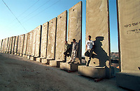 Palestinian men stand next to the concrete 'security wall' separating the Arab east Jerusalem suburb of Sawahreh from Jerusalem, as they wait for taxis, September 29, 2003. The UN General Assembly approved a resolution demanding that Israel halt construction of a barrier cutting the Jewish state off from Palestinian West Bank lands.