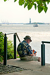 A man sits at the edge of the Granite Prospect stairway at Brooklyn Bridge Park, with a view of the East River and the Statue of Liberty in the background