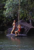 Girls jumping from rope swing into pool. Kalihiwai River, North shore, Kauai