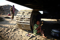 A girl rests in the shade a vehicle's caterpillar tread. At least 10,000 people, including 2,500 women and over 1,000 children, are engaged in stone and sand collection from the Bhollar Ghat on the banks of the Piyain river. Building materials such as stone and sand, and the cement which is made from it, are in short supply in Bangladesh, and commands a high price from building contractors. The average income is around 150 taka (less than 2 USD) a day.