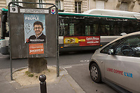 """France. Ile de France. Paris. Partially torn campaign poster of French presidential election candidate<br /> Jean-Luc Mélenchon for the leftist political movement """"Front de Gauche"""" (FG). A public bus rides on the road. A parked Bollore BlueCar Electric car used for Autolib' car sharing service with written words on the side door """" Free as the air"""". 22.04.17 © 2017 Didier Ruef"""