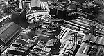 Pittsburgh PA:  Aerial view of Pittsburgh looking southwest at the Pennsylvania Railroad Station and lower strip district.  The image includes railroad yards, terminals, wholesale businesses, warehouses, and manufacturing facilities.
