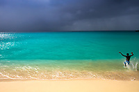 Paradisiac, white sand Maho Beach and turquoise water under a dark, storm sky, with a young man in the water, Sint Maarten, Caribbean Leeward Islands