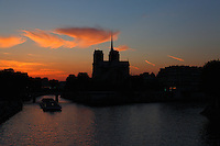 Paris Left Bank: The profile of the back of Notre Dame within its isle, with a tourist boat passing under the bridge,  in the light of an artistic sunset.