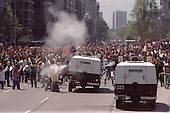"Santiago, Chile.October 1988..After General Pinochet lost a vote to remain in office, hundreds battle police demanding his immediate removal...In October 1988, General Augusto Pinochet ordered a plebiscite vote asking Chilean citizens whether he should continue in office. It produced a decisive ""no"" vote and the following year he lost the first presidential election in 19 years. However, under a constitution crafted by his advisors, he remained as army commander until 1998. Pinochet continued to wield enormous power until his arrest in London on human rights charges in October 1998."