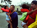Jordyn Taylor, 7, screams as emergency volunteer Mark Garcia, left, and East Hancock County firefighter Wade Hicks Jr. carries her and her twin sister Jody, 7, from the flowing current of Highway U.S. 90 as Hurricane Katrina struck on Monday, August 29, 2005, in Bay St. Louis, Mississippi. The flowing current on the highway over powered and flooded the Taylor family's suburban and forced all 6 people on to the roof.
