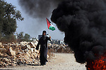 A Palestinian woman holds up her national flag during a protest against Israel's separation barrier as masked Palestinian stones throwers clash with Israeli soldiers in the West Bank village of Bilin, near Ramallah, on November 12, 2010. Clashes erupted during the weekly demonstrations, which are aimed at halting the construction of Israel's controversial separation barrier that is mostly built inside the occupied territory and cuts off farmers from their land in border communities like Nilin. Photo by Issam Rimawi
