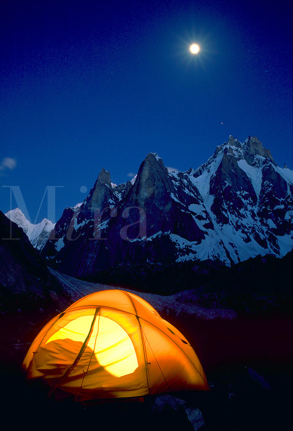 A small tent illuminated at the base of the Hidden Spires of Karakoram Expedition in Pakistan. Snow covered peaks rise in the background against a blue sky.