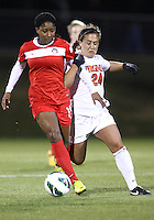 BOYDS, MARYLAND - April 06, 2013:  Tiffany McCarty (14) of The Washington Spirit is held by Danielle Colaprico (24) of the University of Virginia women's soccer team in a NWSL (National Women's Soccer League) pre season exhibition game at Maryland Soccerplex in Boyds, Maryland on April 06. Virginia won 6-3.
