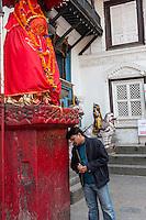 Nepal, Kathmandu.  Middle-aged Man Worshiping at Hanuman Statue, Durbar Square.
