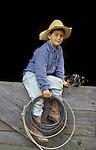 Young cowboy holding a lasso sits in a barn window, his dog alongside.. San Luis Obispo, California   (Garcia Ranch/Joseph/MR)