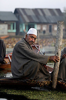 A seller takes a break to smoke a pipe. Floating vegetable market. Srinagar, Kashmir, India. © Fredrik Naumann/Felix Features