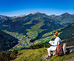 Oesterreich, Tirol, Tuxertal, oberhalb Lanersbach: junge Frau macht Wanderpause auf einer Bank | Austria, Tyrol, Tuxer Valley, above Lanersbach: young woman resting on a bench