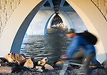A bike rider passes under the Orange Street bridge on the riverfront trail in Missoula, Montana
