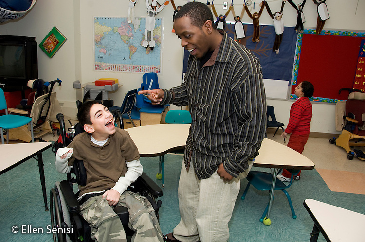 MR / Albany, NY.Langan School at Center for Disability Services .Ungraded private school which serves individuals with multiple disabilities.Teaching assistant (African-American) and child laugh and  interact. Boy: 11, cerebral palsy, expressive and receptive language delays.MR: Bro12; Wes2.© Ellen B. Senisi