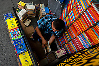 A Salvadoran bookseller stacks books into piles on the street in a secondhand bookshop in San Salvador, El Salvador, 11 April 2018. Large collections of worn-out books, mostly textbooks and educational paperbacks, are sold regularly in secondhand bookshops in the center of the city.