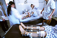 Dr Liu Bin adjusts the metal cage of San Xu who is having her legs lengthened at a Guangzhou hospital. The operation that typically increases height by between 5 - 10 cm (though 16 cm is possible) has been carried out on more than 500 people in China, with varying degrees of success...PHOTO BY SINOPIX