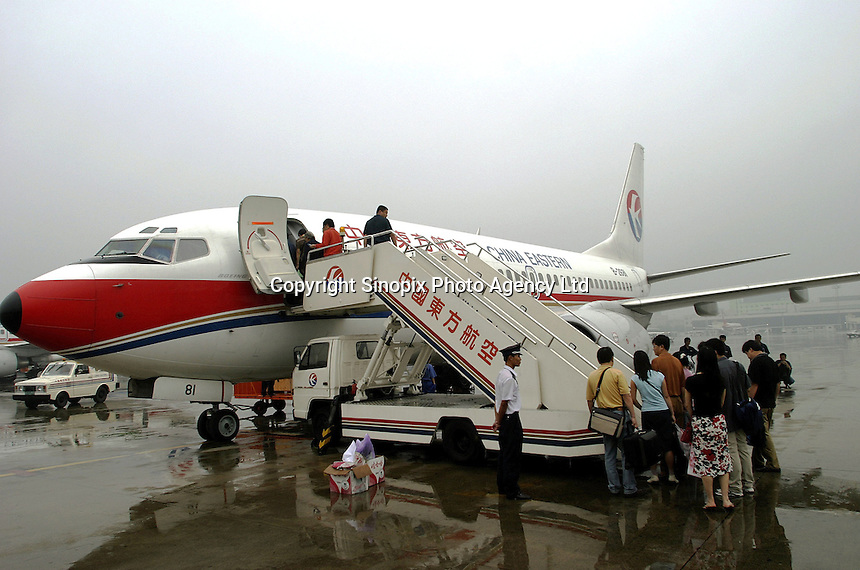 Passengers board a China Eastern Airline Boeiing 737 jet at the Hongqiao Airport in Shanghai, China. China Eastern is one of the largest passenger carriers in China..19-SEP-03