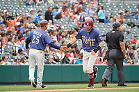 Frisco RoughRiders manager Joe Mikulik (25) high fives Charles Leblanc (12) during a Texas League game against the Midland RockHounds on May 21, 2019 at Dr Pepper Ballpark in Frisco, Texas.  (Mike Augustin/Four Seam Images)