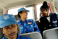 """LIBERIA, Monrovia, 05/04/2007..Itee keeps a close eye on Winnefred, a Liberian National Police officer, whilst on Joint Task Force patrol in the Duport Rd area of Monrovia. """"On the Job"""" training forms a vital aspect of the unit's role in helping to build capacity in the Liberian National Police Force...© 2007 Aubrey Wade. All rights reserved.2"""