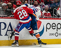 WASHINGTON, DC - JANUARY 31: Johnny Boychuk #55 of the New York Islanders  and Brendan Leipsic #28 of the Washington Capitals  battle along the boards during a game between New York Islanders and Washington Capitals at Capital One Arena on January 31, 2020 in Washington, DC.