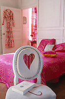A heart decorates a Louis XVI chair and the bed is covered in pink silk in this feminine bedroom