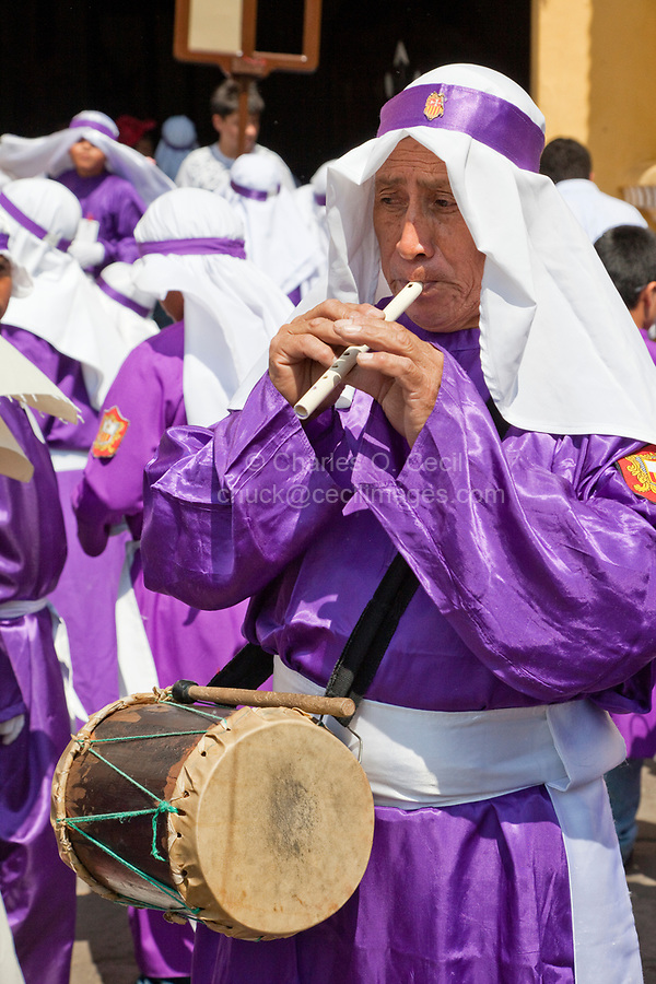 Antigua, Guatemala.  A Cucurucho Plays a Mayan Flute and Carries a Drum while Accompanying a Religious Procession during Holy Week, La Semana Santa.