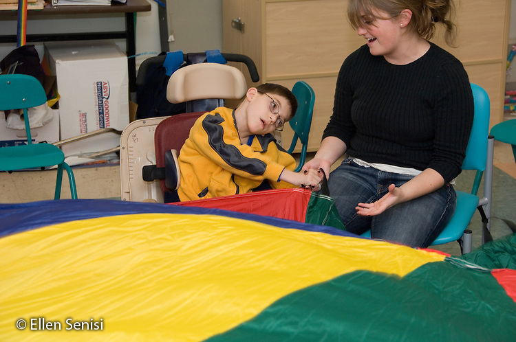 MR / Albany, NY.Langan School at Center for Disability Services .Ungraded private school which serves individuals with multiple disabilities.Child holds parachute with teaching assistant during lesson with the objective of helping develop coordination and grasping skills while playing. Boy: 9, cerebral palsy, limited verbal output with expressive and receptive language delays.MR: Rub1, Ken8.© Ellen B. Senis