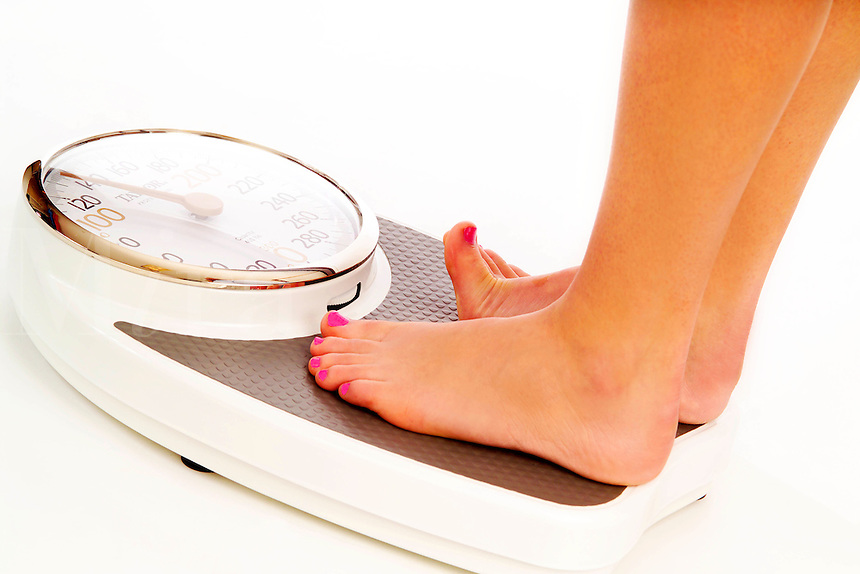 Close up of a woman's feet standing on a bathroom weight scale