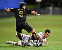 LAKE BUENA VISTA, FL - JULY 18: Cristian Pavón #10 of LA Galaxy dribbles falls on top of the ball in front of Dejan Jakovic #5 of LAFC during a game between Los Angeles Galaxy and Los Angeles FC at ESPN Wide World of Sports on July 18, 2020 in Lake Buena Vista, Florida.