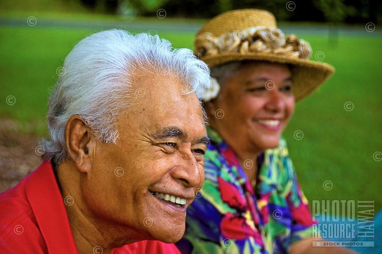 Smiling senior Hawaiian man and part-Hawaiian woman with hat