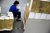 """An Amity Printing Company employee examines the quality of newly-printed gold-edged Bibles in the Amity Printing Company's new printing facility in Nanjing, China....On May 18, 2008, the Amity Printing Company in Nanjing, Jiangsu Province, China, inaugurated its new printing facility in southern Nanjing.  The facility doubles the printing capacity of the company, now up to 12 million Bibles produced in a year, making Amity Printing Company the largest producer of Bibles in the world.  The company, in cooperation with the international organization the United Bible Societies, produces Bibles for both domestic Chinese use and international distribution.  The company's Bibles are printed in Chinese and many other languages.  Within China, the Bibles are distributed both to registered and unregistered Christians who worship in illegal """"house churches."""""""