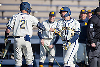 Michigan Wolverines first baseman Jimmy Obertop (8) is greeted by Benjamin Semi (2) after hitting a home run during the NCAA baseball game against the Illinois Fighting Illini at Fisher Stadium on March 19, 2021 in Ann Arbor, Michigan. Illinois won the game 7-4. (Andrew Woolley/Four Seam Images)