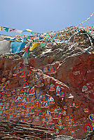 Painted rock carvings of revered Buddhist figures along the prayer-flag lined walkway up Chagpo Ri mountain, part of the sacred Lingkhor pilgrim circuit, which encircles the old city, Lhasa, Tibet, China.