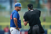 Kannapolis Cannon Ballers manager Guillermo Quiroz (40) discusses a call with home plate umpire Zee Zdenek during the game against the Carolina Mudcats at Atrium Health Ballpark on June 10, 2021 in Kannapolis, North Carolina. (Brian Westerholt/Four Seam Images)