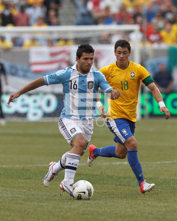 Argentina substitute forward  Sergio Aguero (16) drives for the net as Brazil substitute midfielder Giuliano (18) defends. In an international friendly (Clash of Titans), Argentina defeated Brazil, 4-3, at MetLife Stadium on June 9, 2012.