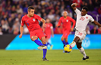 ORLANDO, FL - NOVEMBER 15: Aaron Long #3 of the United States sends a ball downfield past Jonathan David #20 during a game between Canada and USMNT at Exploria Stadium on November 15, 2019 in Orlando, Florida.