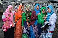 """Borobudur, Java, Indonesia.  Young Women from Surabaya Visiting the Temple.  The V is a common gesture in Indonesia when the person being photographed wants the photo to be a good one.  The raised thumb and straight index finger (lady on the left) means """"looking good."""""""